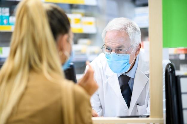 Leitender apotheker, der mit einem kunden zu tun hat, beide tragen aufgrund des coronavirus masken