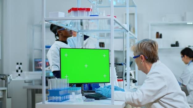 Leitender arzt, der am computer mit grünem bildschirm im modern ausgestatteten labor arbeitet. multiethnisches team von mikrobiologen, die impfstoffforschung betreiben und auf einem gerät mit chroma-key schreiben, isoliert, mockup-display.
