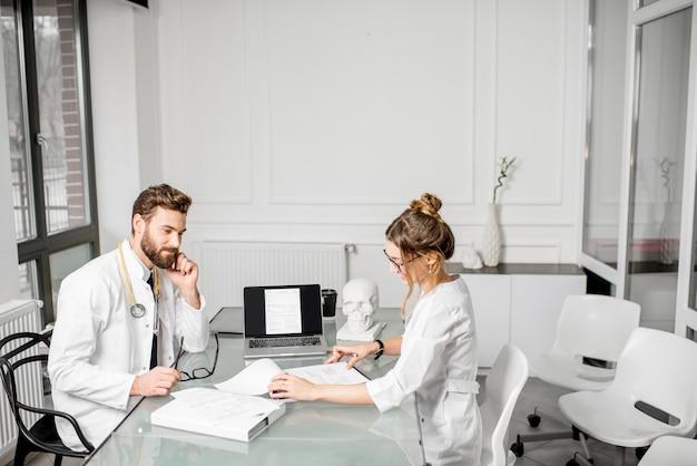 Leitender arzt mit junger assistentin, die an medizinischen dokumenten arbeitet, die zusammen im weißen büroinnenraum sitzen. weitwinkelaufnahme mit kopienraum