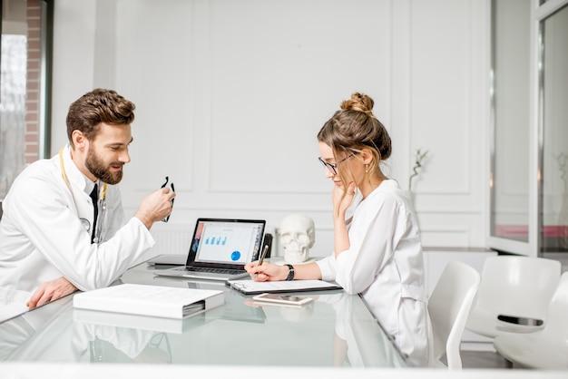 Leitender arzt mit junger assistentin, die an medizinischen dokumenten arbeitet, die zusammen im weißen büroinnenraum sitzen
