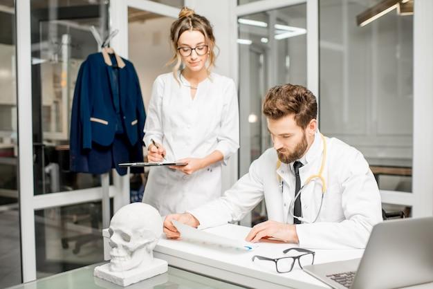 Leitender arzt mit junger assistentin, die im weißen büro mit medizinischen dokumenten arbeitet