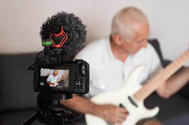 Leitender gitarrist, der ein video von sich selbst aufnimmt, während er im heimstudio eine e-gitarre spielt