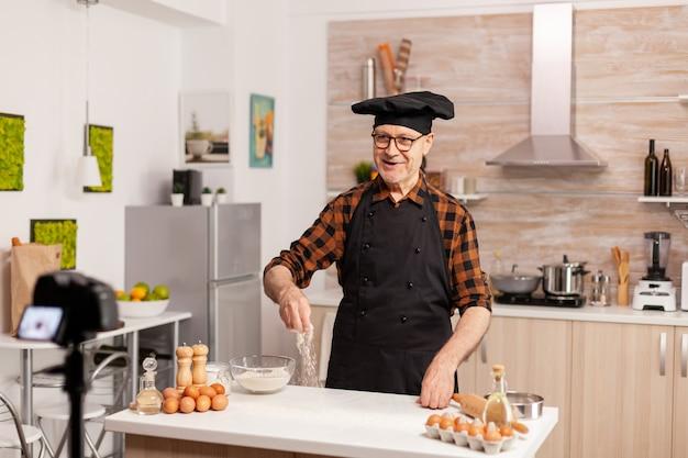 Leitender koch in der heimküche, der ein tutorial zum kochen aufnimmt. pensionierter blogger-bäcker-influencer, der internet-technologie verwendet, um mit digitaler ausrüstung zu kommunizieren, zu schießen, zu bloggen in sozialen medien