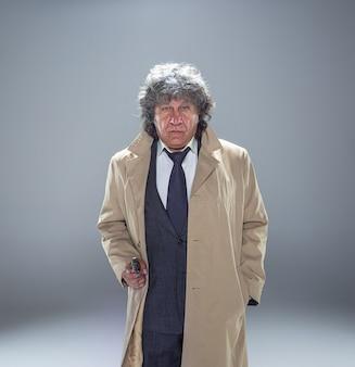 Leitender polizeibeamter mit einer waffe als detektiv oder mafia-chef. studioaufnahme auf grau im retro-stil