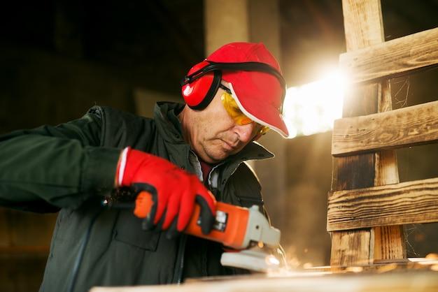 Leitender schreiner, der mit elektrischem schleifwerkzeug auf der holzpalette in einer professionellen uniform arbeitet.
