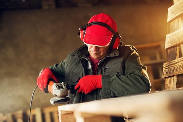 Leitender schreiner, der mit elektrischem schleifwerkzeug in einer professionellen uniform arbeitet.