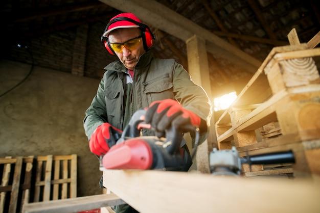 Leitender schreiner in berufsuniform, der mit einer maschine in der holzwerkstatt arbeitet.