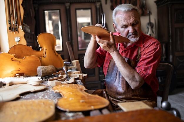 Leitender schreinerhandwerker, der die klangqualität des holzmaterials in seiner altmodischen tischlerwerkstatt überprüft