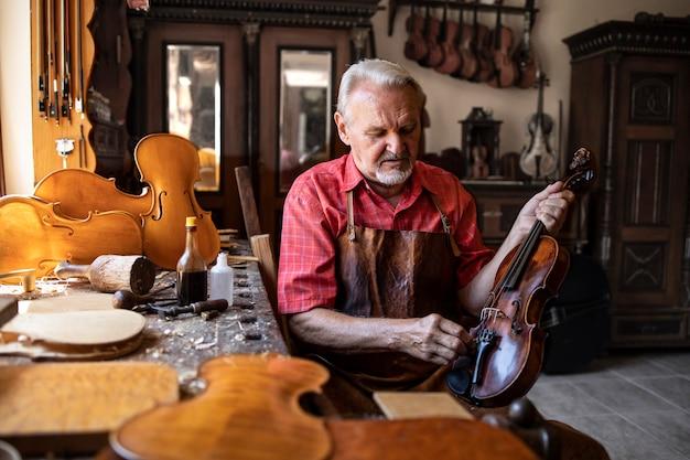 Leitender schreinerhandwerker, der geigeninstrument in seiner tischlerwerkstatt poliert