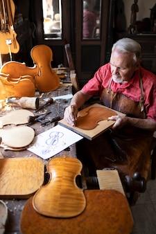Leitender schreinerhandwerker, der geigenmusikinstrument in seiner altmodischen tischlerwerkstatt macht