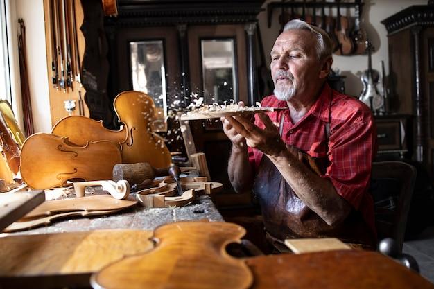 Leitender schreinerhandwerker, der mit hartholz in der werkstatt arbeitet und sägemehl abbläst