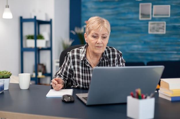 Leitender unternehmer, der ohne brille von einem tragbaren computer liest