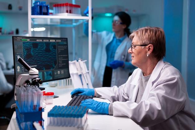 Leitender wissenschaftler, forscher, der einen impfstoff entwickelt, mit einem team in einer pharmakologischen chemieanlage