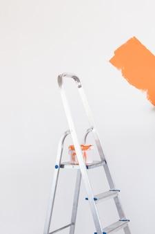 Leiter mit farbe im eimer in der nähe der farbwand im innenbereich. renovierungs- und renovierungskonzept.