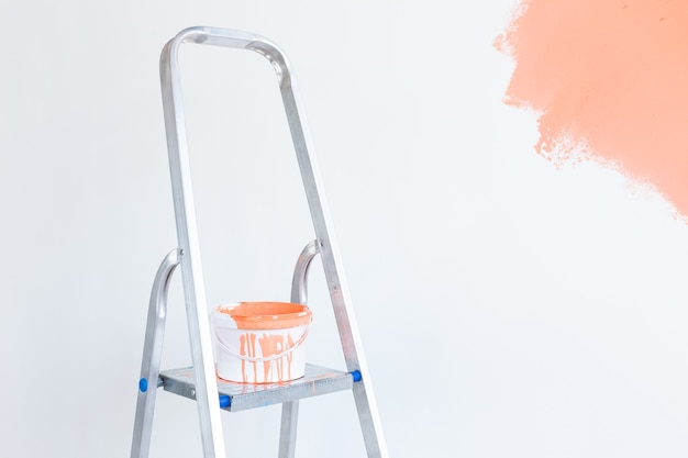 Leiter mit farbe im eimer nahe farbwand drinnen. renovierungs- und renovierungskonzept.
