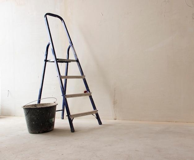 Leiter und eimer auf einer weißen hintergrundwand mit kopienraum. hintergrund des konzepts des objekts im bau.