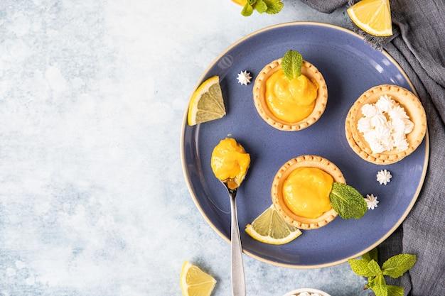 Lemon curd mini-törtchen dekoriert mit minze und zitronenscheiben auf blauem keramikteller