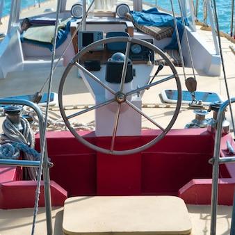 Lenkrad auf der yacht mit blauem meerwasserhintergrund