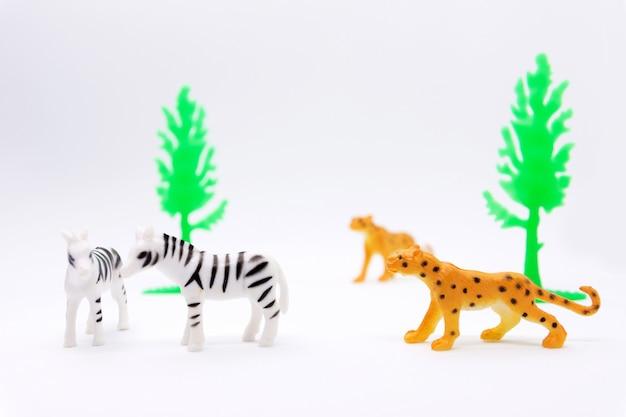 Leopard- und zebra-modell lokalisiert auf weißem hintergrund, tier spielt plastik