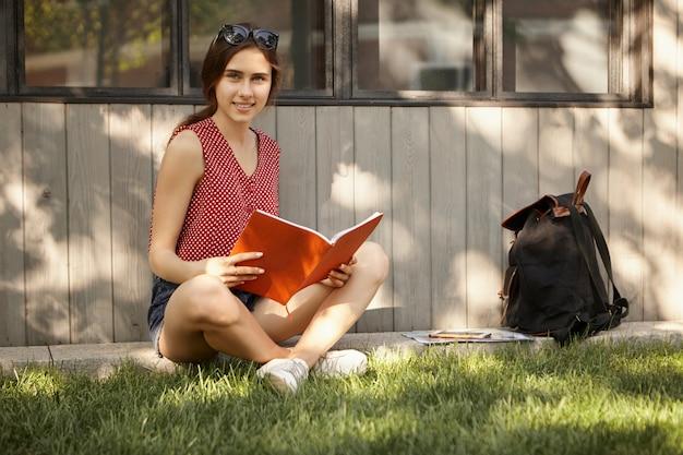 Lern-, bildungs-, menschen- und lifestyle-konzept. sommerzeitbild des schönen studentenmädchens, das auf grünem gras im park sitzt, beine gekreuzt hält, heft mit vorlesungen hält, sich auf prüfung vorbereitet