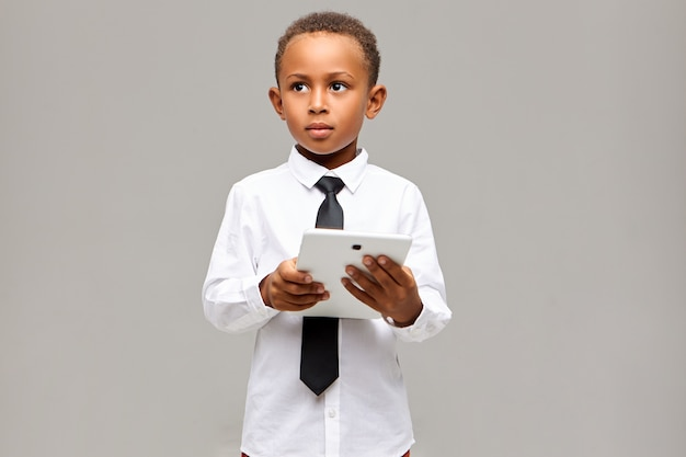 Lern-, bildungs-, technologie- und kommunikationskonzept. hübscher kluger afrikanischer student in der schuluniform, die mit digitalem touchpad-tablett unter verwendung der drahtlosen internetverbindung aufwirft