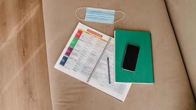 Lernbücher mit telefon und maske auf der couch zu hause. online-bildung