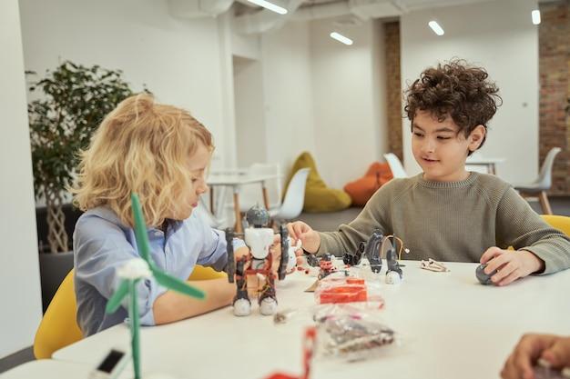 Lerne aus eigener erfahrung fröhliche kleine jungs, die sitzen und roboter untersuchen und mit ihnen spielen
