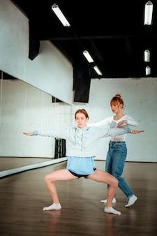 Lerne hocken. dunkelhaariger hübscher teenager, der schwarze shorts trägt und in der tanzstunde hockt