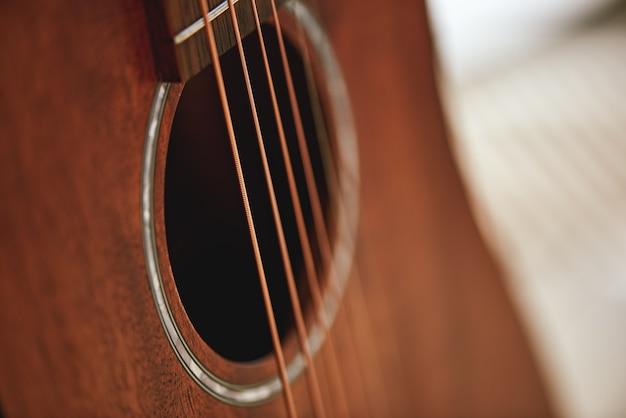 Lernen sie ihr instrument kennen. nahaufnahme foto von akustikgitarre schallloch. musikanlage. musikinstrumente. musikkonzept