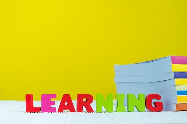 Lernen sie textalphabet und stapel des buches mit gelbem hintergrund.