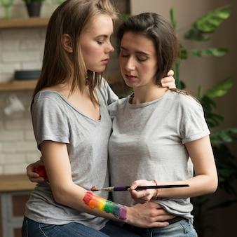 Lesbenfrau, die regenbogenflagge auf der hand ihrer freundin malt