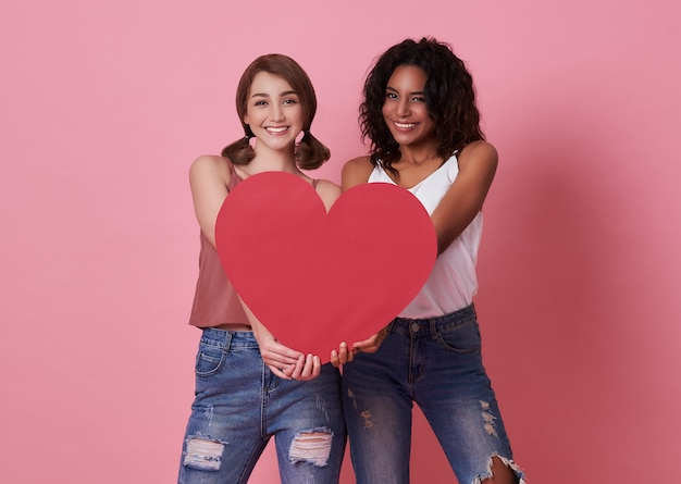 Lesbenpaar stehend und hand, die rotes herz für valentinstag halten.