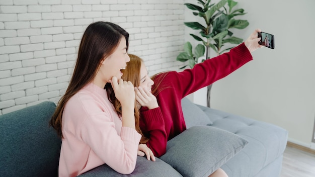 Lesbische asiatische paare unter verwendung des smartphone selfie im wohnzimmer zu hause