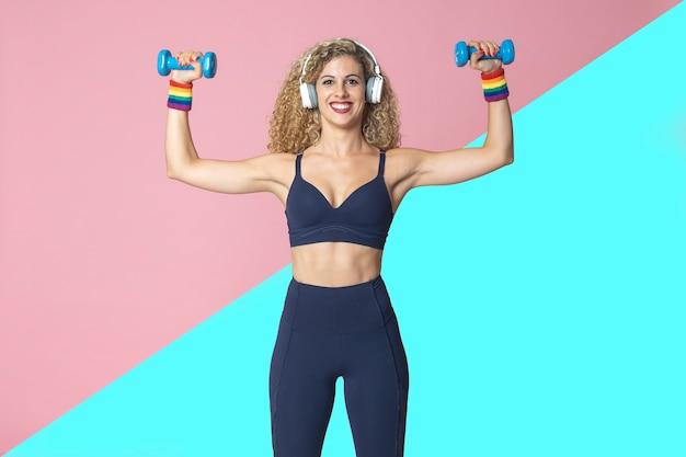 Lesbische frau mit eignungslebensstilsportpraxis führt gewichtstrainingsübungen durch, die musik mit kopfhörern hören