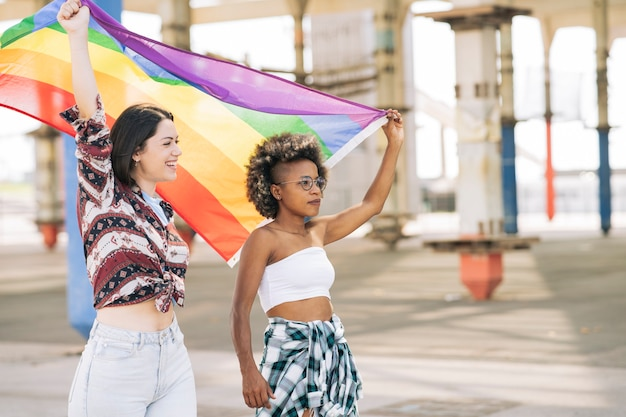 Lesbische frauen protestieren, während sie eine lgbt-flagge auf der straße halten