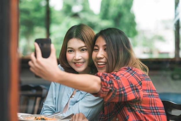 Lesbische lgbt paare der schönen glücklichen asiatischen frauen, die jede seite essen eine platte der italienischen meeresfrüchte sitzen