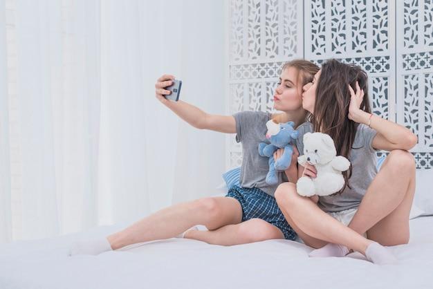 Lesbische paare, die auf dem bett hält die weichen spielwaren nehmen selfie am handy sitzen