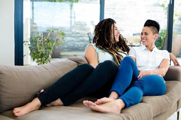 Lesbische paare, die miteinander im wohnzimmer lächeln und sprechen