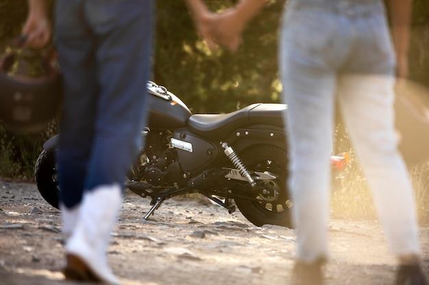 Lesbisches paar händchen haltend in der nähe von motorrad während eines roadtrips