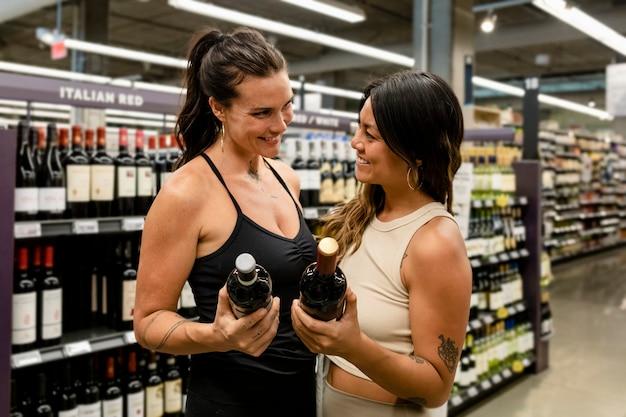 Lesbisches paar kauft wein, supermarkt kauft hd-bild ein
