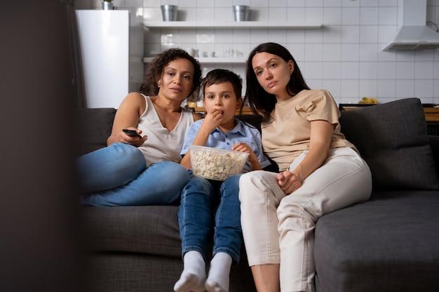 Lesbisches paar mit sohn schaut sich einen film an