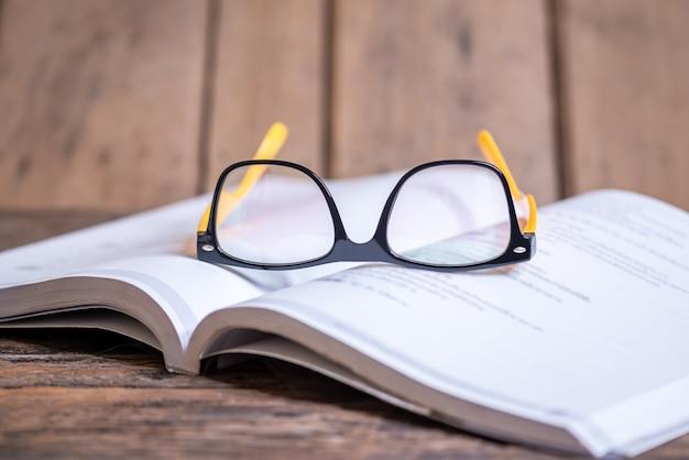 Lese- und wissenskonzept, brille auf dem buch unscharfer hintergrund