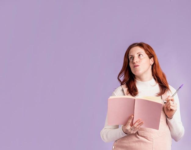 Lesebuch der schwangeren frau mit niedrigem winkel mit kopienraum