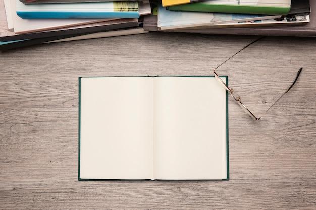 Lesekonzept mit brille neben leerem buch