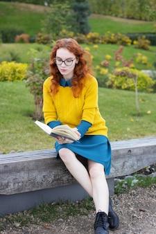 Lesekopfmädchen, das in einem park mit buch sitzt