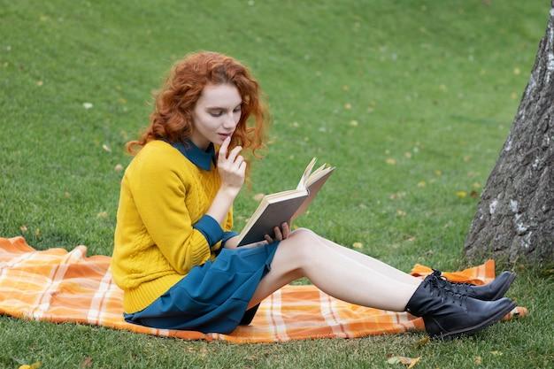 Lesekopfmädchen, das in einem park sitzt