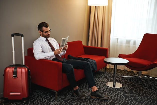 Lesen neuer nachrichten. brillenträger mit koffer und zeitung auf dem sofa in der hotelhalle sitzend