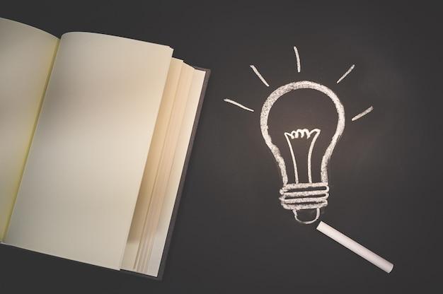 Lesen sie ein buch konzept glühbirne symbol an der tafel repräsentiert eine idee