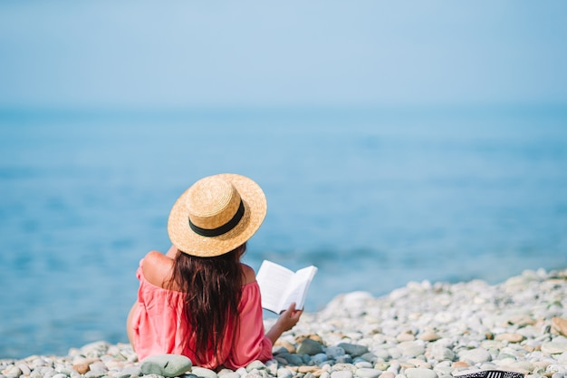 Lesesuch der jungen frau während des tropischen weißen strandes