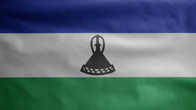 Lesotho-flagge weht im wind. nahaufnahme von sesotho banner weht, weiche und glatte seide. stoff textur fähnrich hintergrund. verwenden sie es für das konzept für nationalfeiertage und länderanlässe.